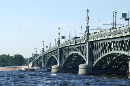 Boat coming from under Troitsky Bridge in Saint Petersburg Stock Photo