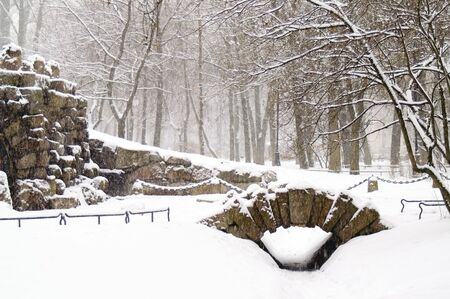 A grotto and a small bridge in a winter park at snowfall. Stock Photo