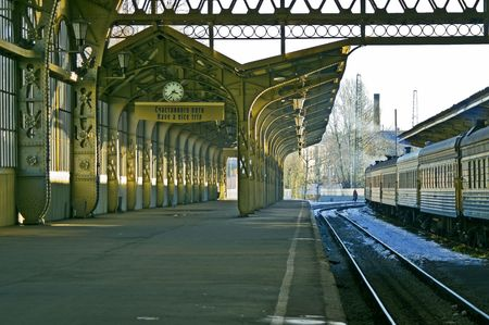 constructivism: Railroad station platform with a hanging clock and Have a nice trip signboard.