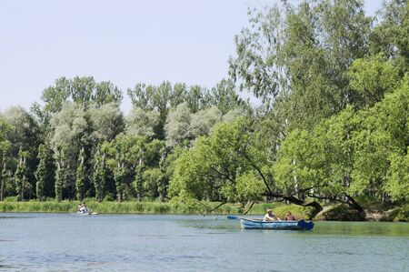 Boaters - People boating in a summer park.