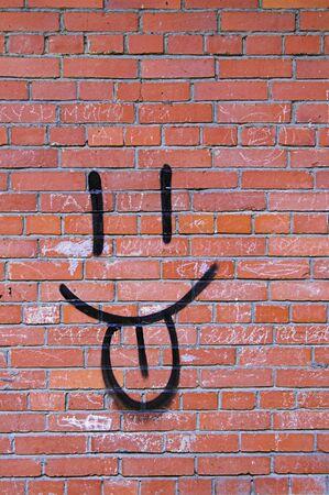 Brick Wall and Smile Graffiti - 2 - Smile Graffiti on a Red Brick Wall. Stock Photo