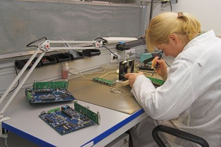 Engineer working with circuits - A woman engineer solders circuits sitting at a table