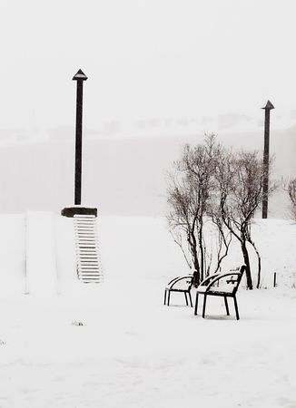 Benches at a back alley while snowing heavily.