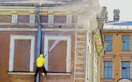 Cleaning service worker washing old building facade photo