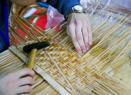 Boy doing traditional crafting work of basketry Stock Photo
