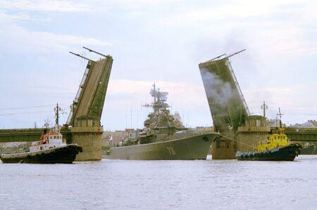 A naval craft tugged through raised Schmidts drawbridge over Neva river in Saint Petersburg, Russia.