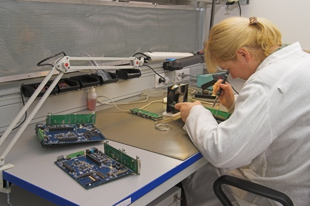 soldered: Engineer working with circuits - A woman engineer solders circuits sitting at a table