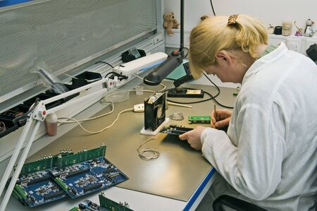 A woman engineer solders circuits sitting at a table  Stock Photo - 13204487