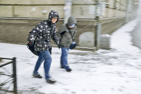 ST PETERSBURG, RUSSIA-FEBRUARY 15, 2008: Unidentified boys trying to break through heavy snowstorm and blizzard in city street Stock Photo - 8652838