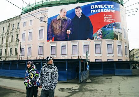 ST PETERSBURG, RUSSIA-MARCH 02, 2008: Citizens pass by banner for presidential election campaign showing President Vladimir Putin and Candidate Dmitri Medvedev. Slogan reads: Together We Will Win---  A huge ad banner that was used for presidential electio