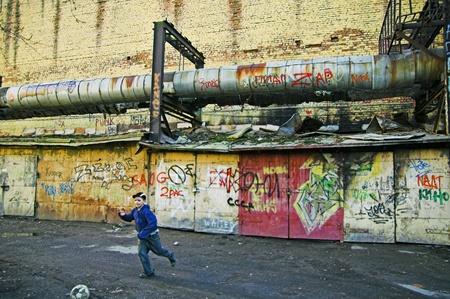 underprivileged: ST PETERSBURG, RUSSIA-aprile 12, 2008: Ragazzo giocando a calcio in una zona povera nella periferia della citt� di San Pietroburgo, Russia