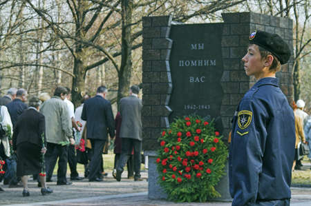 ST PETERSBURG - MAY 5: March in memory of WWII victims in city Victory Park. Schoolboy, 13, in scout uniform on honor guard May 5, 2008 in St Petersburg, Russia. Slogan on monument: We Remember You