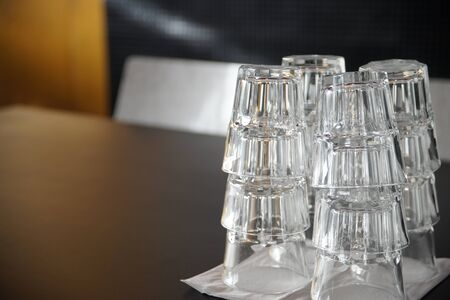 Clean drinking glasses stacked on a black table in a cafe. Stock Photo