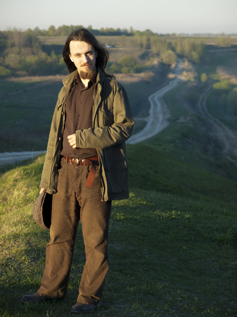 A young man stands on a grass hill in a sunny spring evening. A field and a road are in the background. The man has lond dark hair and a beard, dressed in brown and holds a cap in his hand. Stock Photo