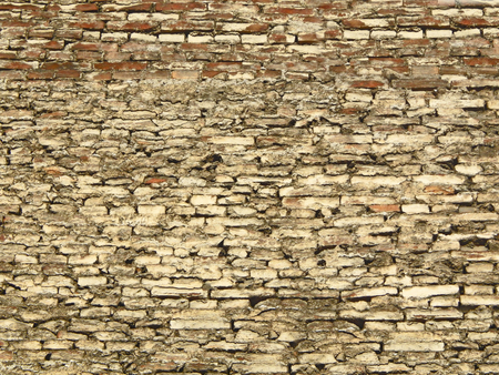 Textured background of a grey-brown brick wall of irregular bricks