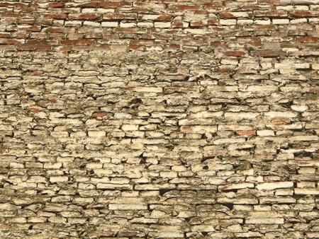 Textured background of a grey-brown brick wall of irregular bricks