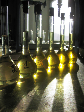 A raw of measuring flasks filled with yellow liquid and closed with rubber plugs. Old-stile chemical lab interior. The golden light shines in the flasks and reflects on a table surface. Still-life. Stok Fotoğraf