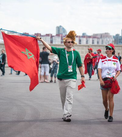 Football fans of Morocco at 2018 FIFA world cup in Russia. A man holds a red flag with a star and wears a lion hat. A girl has a flag painted on her cheek.