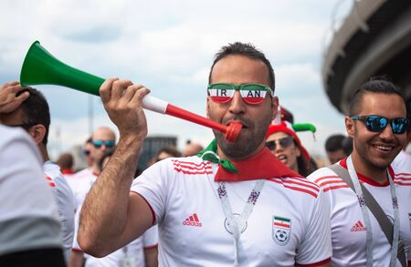 Football fans of Iran at 2018 FIFA world cup in Russia. A wan in glasses colored as iranian flad is tootling a pipe