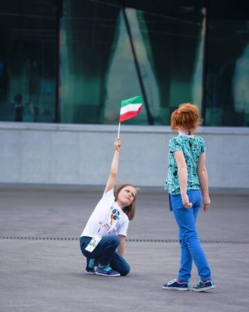 Football fans of Iran at 2018 FIFA world cup in Russia. Two little girls are playing with the iranian flag
