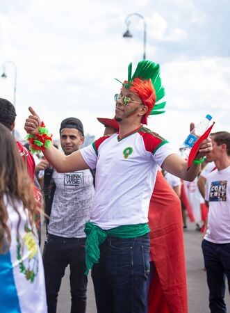 Football fans of Morocco at 2018 FIFA world cup in Russia. A man with color mohawk hairdo
