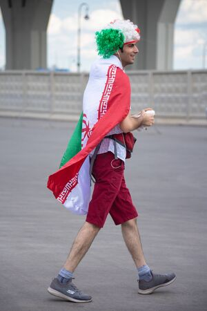 Football fan of Iran at 2018 FIFA world cup in Russia. The man is dressed in Iranian flag of red, white and green