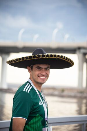 A football fan of Mexico at 2018 FIFA world cup in Russia in large sombrero hat and green T-shirt