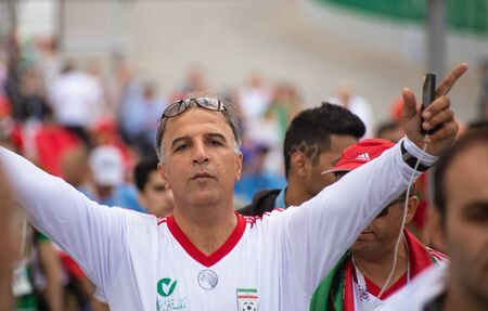 A football fan of Iran in white shirt at 2018 FIFA world cup in Russia is raising his hands Editorial