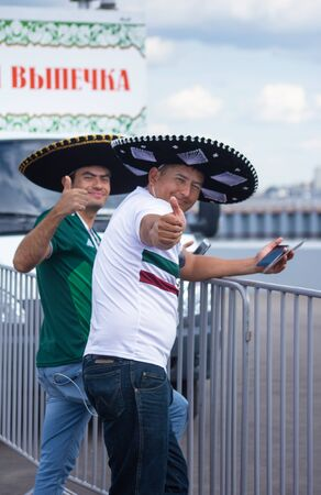 Two football fans of Mexico at 2018 FIFA world cup in Russia in large sombrero hats are standing near the enclosure