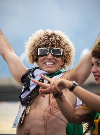 A football fan of Iran at 2018 FIFA world cup in Russia with funny wig, glasses and tattoos is laughing Editorial