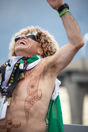 A football fan of Iran at 2018 FIFA world cup in Russia with funny wig, glasses and tattoos is laughing loudly
