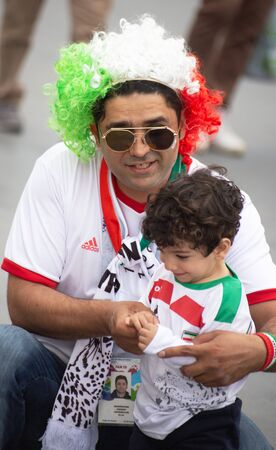 Football fans of Iran at 2018 FIFA world cup in Russia. A man in tricolor hat with his son