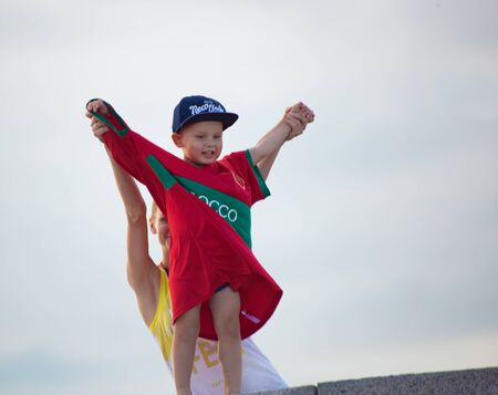 Football fan of Morocco at 2018 FIFA world cup in Russia. A little boy in a big T-shirt of Morocco colors