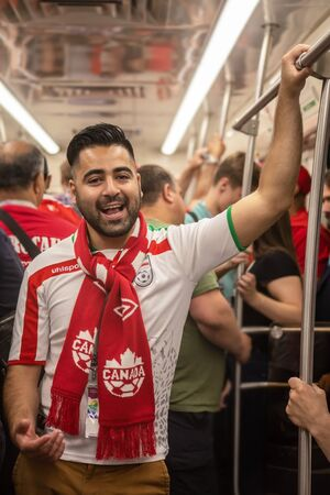 Football fan of Iran at 2018 FIFA world cup in Russia in the subway. The man in Iranian uniform is wearing a Canadian scarf Editorial