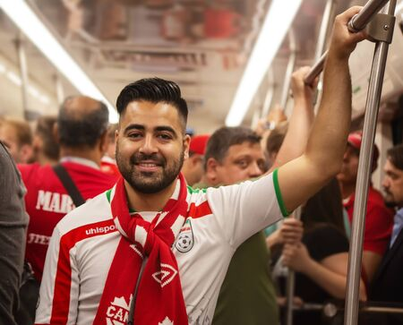 Football fan of Iran at 2018 FIFA world cup in Russia in the subway. The man in Iranian uniform is wearing a Canadian scarf and smiling Editorial