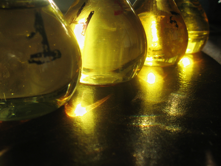 A raw of measuring flasks filled with yellow liquid. Old-stile chemical lab interior. The golden light shines in the flasks and reflects on a table surface. Still-life. Standard-Bild