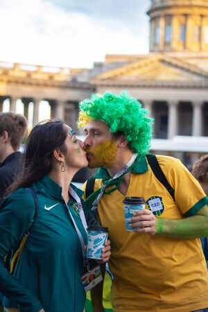 Two football fans of Brasil kiss in front of Kazan cathedral in St. Petersburg, Russia. July 2018, FIFA world cup.