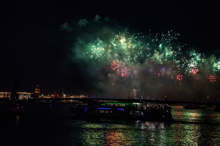 A green and red firework display in the night sky over Trinity bridge across river Neva at Scarlet Sails festivity in Saint Petersburg ,Russia