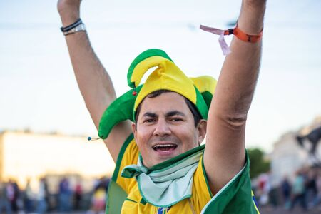 Still happy football fan of Brasil in a yellow and green hat raised his arms. St. Petersburg, Russia. July 2018, FIFA world cup. Editorial