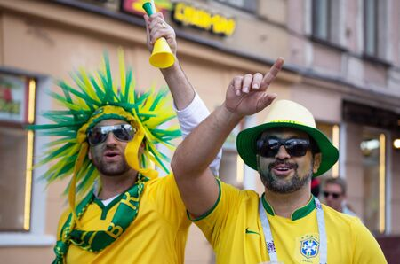 Two still happy football fan of Brasil in a yellow and green hat raised their arms. Nevskiy prospekt, St. Petersburg, Russia. July 2018, FIFA world cup. Editorial