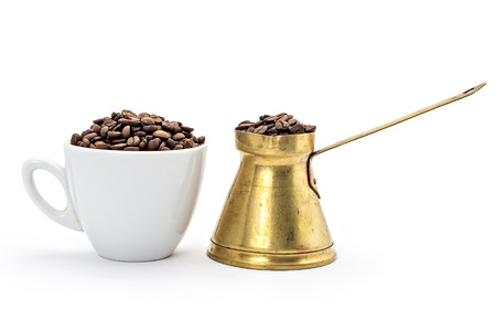 coffeebeans: White coffee cup and traditional old brass coffee pot with long handle filled with coffeebeans isolated on white
