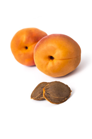 pits: Two apricot pits and fresh ripe organic apricots isolated on white background