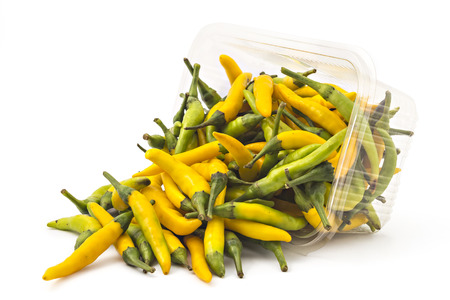 accomplishment: Box or punnet and spilled fresh hot peppers isolated on white background