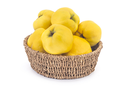 quinces: Fresh ripe yellow quinces in woven basket isolated on white background