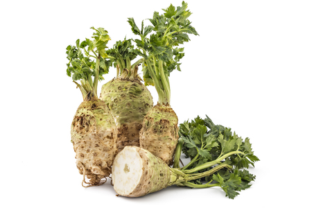 Three fresh organic celery roots with leaves and one cutted on a white background Stock Photo