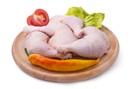 Fresh raw chicken legs arrangement on kitchen cutting board with lettuce, tomato and pepper