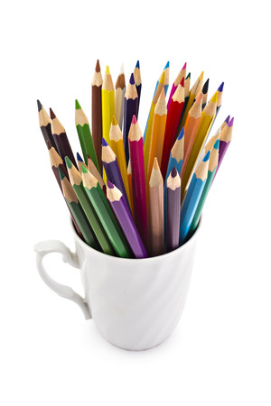 A stack of colored pencils of various color in a rustic white cup on white background