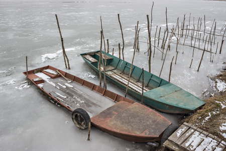 Two old wooden boat, one wrecked in a frozen river Tisa near Becej, Serbia. Winter time Stock Photo