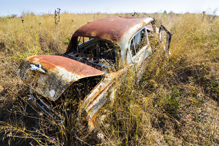 An abandoned and degraded old junk car left in the grassy meadows. Scrapyard