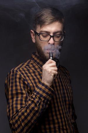 man with a beard wearing glasses on black background smoke vape